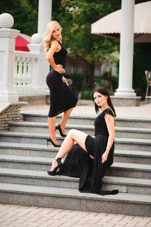 two young pretty woman in a black dress.