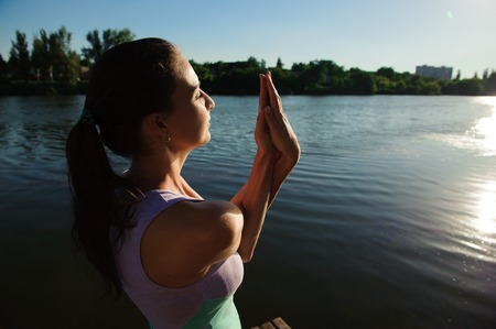 Young healthy woman practicing yoga on the bridge in the nature. 写真素材