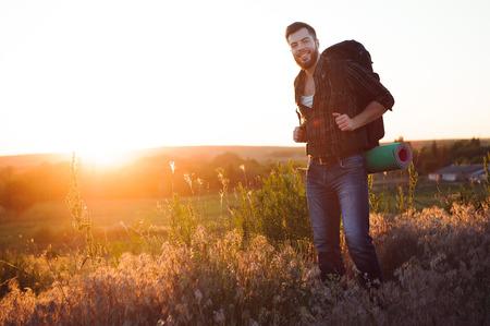 Viajero con mochila de pie sobre una roca y disfrutando del atardecer.