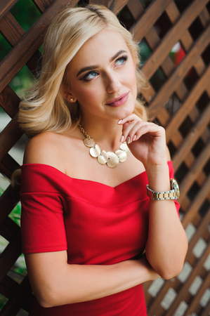 Young attractive female blonde woman in red dress sitting on chair 写真素材