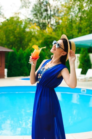 Beauty and vacation. Pretty young woman near swimming pool 写真素材