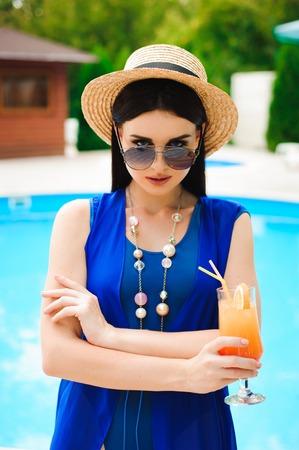 Beautiful brunette woman wearing a blue bikini, enjoying the pool, summer time Фото со стока