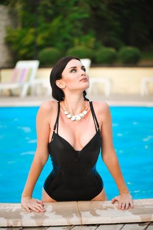 Portrait of beautiful tanned woman in black swimwear relaxing in swimming pool spa