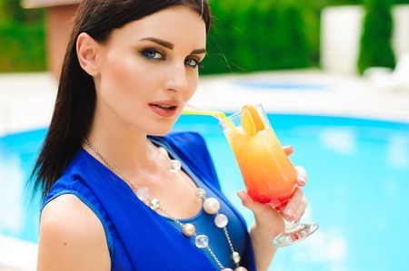 Enjoying summer. Beautiful young woman drinking cocktail while relaxing near the pool
