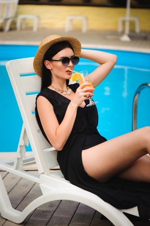 Young tan model in stylish summer outfit enjoying pool party , holding tasty alcohol cocktail. 写真素材