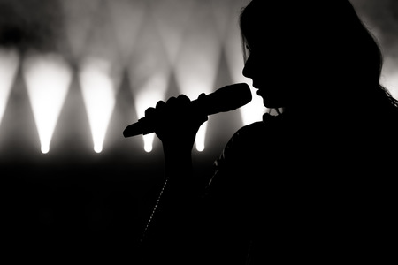 Singer in silhouette. Close up image of live singer on stage Stock Photo