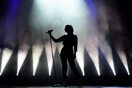 Sänger singt zum Mikrofon. Sänger in Silhouette
