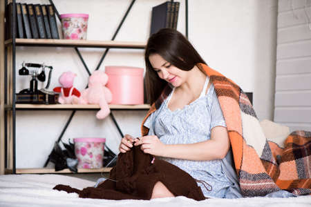 A pregnant woman knits for her unborn child on the bed at home.