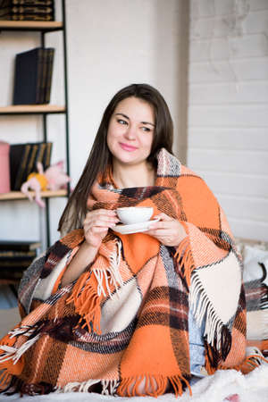 Pregnant woman drinking tea in bed at home.
