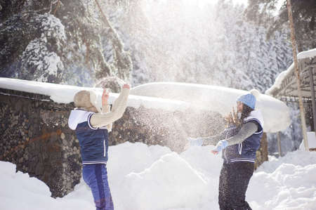 Two girlfriends have fun and enjoy fresh snow on a beautiful winter day
