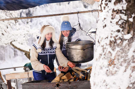 Two girlfriends cooking in the winte nature on a fire in the boiler. Girls bask in the fire in winter. 版權商用圖片