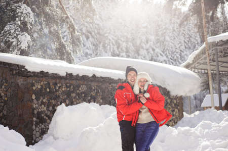 Couple in love holding hands and playing with snow outdoor in winter.