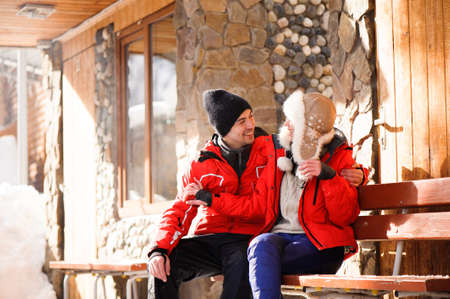 family couple in a winter clothes sitting on a wooden bench