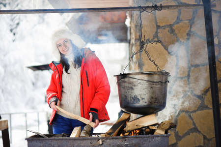 Beautiful woman cooking dinner in the winter outdoors.