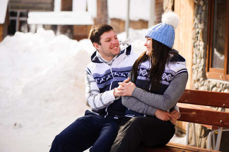 Happy couple in love hugging and kissing at winter resort