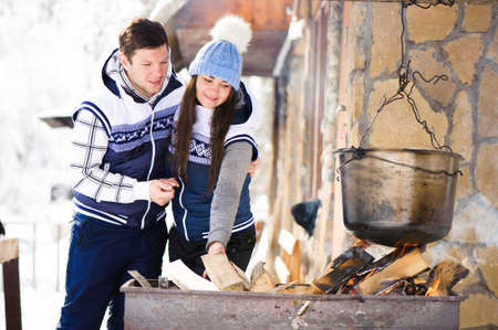 Family in love laughing and cooking in the winter outdoors. Bonfire, barbecue, bowler.