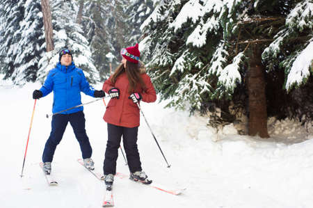 happy married couple skiing at a ski resort in the forest 版權商用圖片