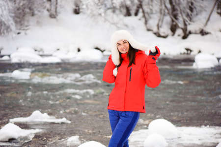 Young beautiful girl in the winter forest near the river