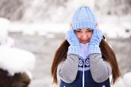 Beautiful young woman smiling and playing with snow in winter season 版權商用圖片