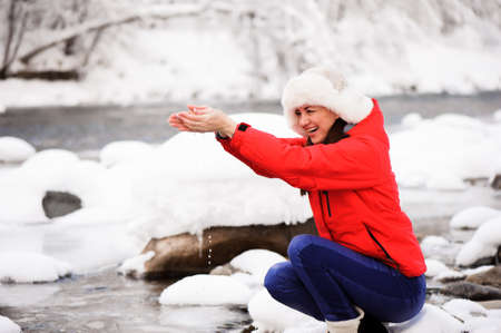 A young girl in a winter park on a walk. Christmas holidays in the winter forest near the river. 版權商用圖片