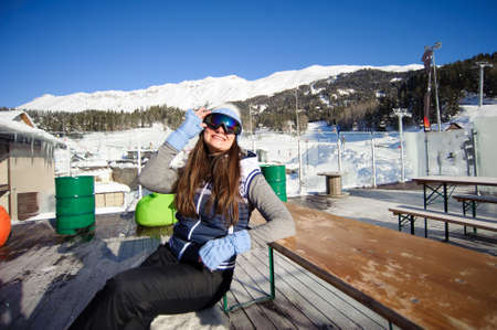 girl resting from skiing in a cafe ski resort at the foot of the mountains
