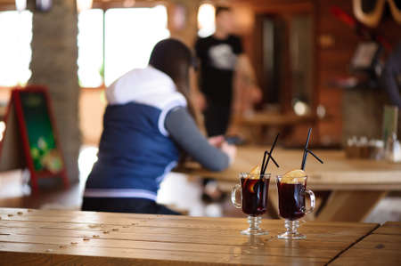 two glasses with hot tasty mulled wine on a wooden table in a cafe 版權商用圖片