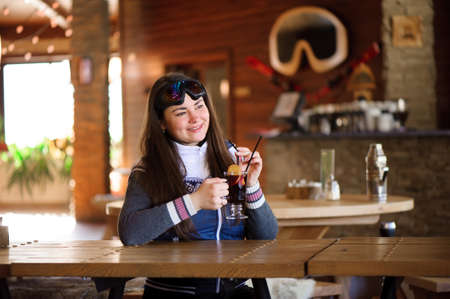 girl resting and drinking hot tasty mulled wine in a cafe ski resort