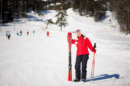 Winter holiday and sport concept with woman with skis in her hands at the foot of the mountain 版權商用圖片