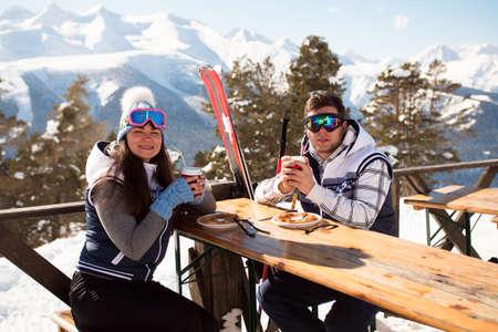 Winter, ski - skiers enjoying lunch in winter mountains.