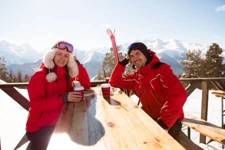 Two lovers and friends enjoying drink in bar at ski resort.