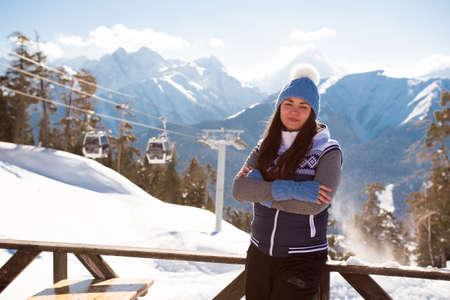 Girl-skier on the hill posing in interior of verandah of cafe at a ski resort