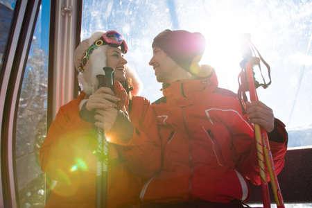 cheerful friends on ski lift ride up on snowy mountain 版權商用圖片