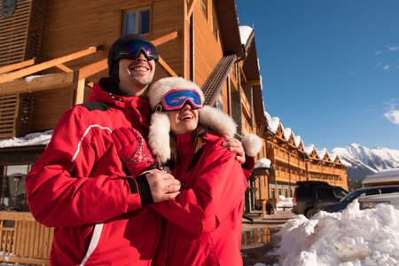 Couple enjoying view of cottages and chalets in a ski resort