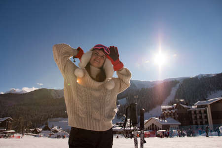 Winter holiday and sport concept with woman with skis at the foot of the mountain. 版權商用圖片