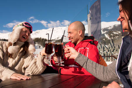 Group of happy friends cheering with drink after skiing day in cafe at ski resort.