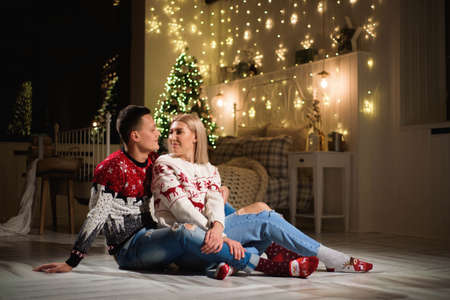 Couple in knit sweaters near Christmas tree. Man and woman in Christmas interior room.