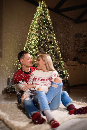 Lovely couple sitting on carpet wearing christmas sweater and hugging.