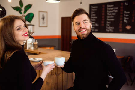 Beautiful Woman And Handsome Man Drinking Coffee While Spending Time In Coffee Shop.