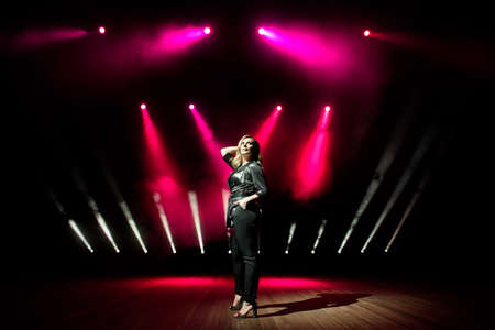 Young woman singer with colorful lights on concert