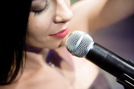 Female singer, performing her vocal sound on the scene with spotlight.
