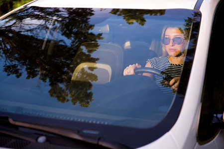 Attractive cheerful girl driver sits in the drivers seat of a modern car Imagens