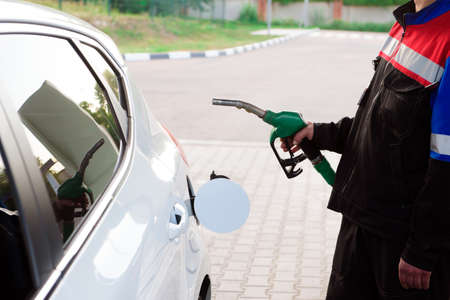 Gas station worker in workwear refueling luxury car with gasoline holding filling gun at the station.