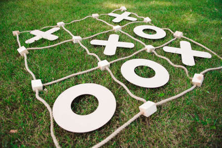Tic tac toe game on the green grass.