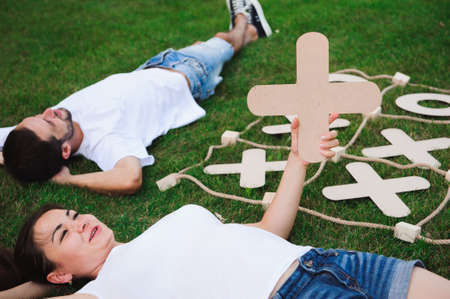 Friends rest and play tic-tac-toe on the green grass.