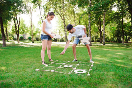 Boy and girl playing tic-tac-toe in the park.