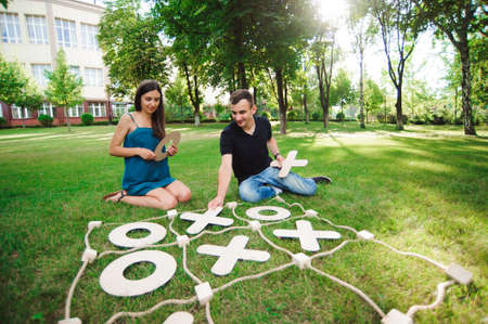 Big Tic Tac Toe game. Guy and girl playing outdoors.