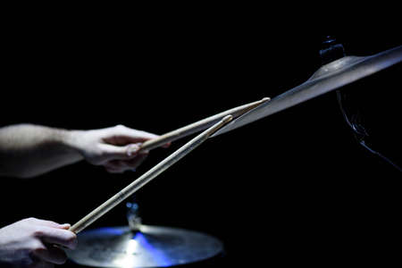 man plays musical percussion instrument with sticks closeup on a black background, a musical concept with the working drum, beautiful lighting on stage Foto de archivo