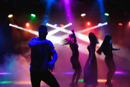 party, holidays, celebration, nightlife and people concept - group of happy friends dancing in night club
