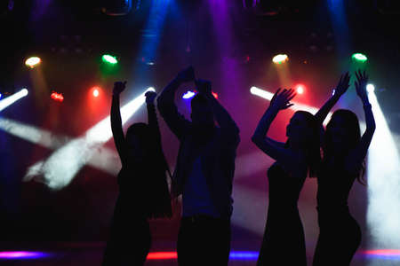 party, holidays, celebration, nightlife and people concept - group of happy friends dancing in a night club