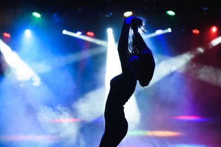 Dancing silhouette of girl in a nightclub. Foto de archivo